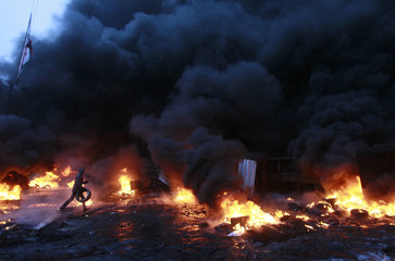 A pro-European protester carries a tyre to burn during clashes with riot police in Kiev