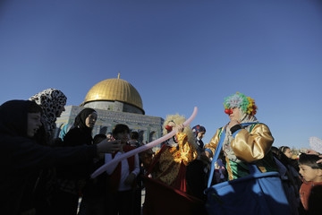 Palestinians look at clowns performing in front of the Dome of the Rock in Jerusalem's Old city, on the first day of Eid al-Adha
