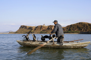 A North Korean fisherman pilots a boat with fish hawks perched onboard, in the Yalu River near the North Korean town of Sinuiju, facing the Chinese border city of Dandong