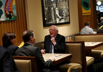 Democratic U.S. presidential candidate Bernie Sanders laughs after sitting down for breakfast at Lou Mitchell's Restaurant in Chicago, Illinois