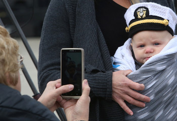 A woman takes a photo of a baby wearing a sailor hat during the commissioning of the USS Illinois, the 13th ship of the Virginia class of submarines, Groton