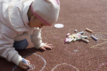 little girl draws a chalk