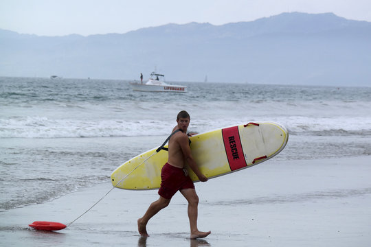 Lifeguard carries a rescue board on the beach after a lightning strike injured people in the water in Venice