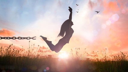 Freedom concept: Silhouette of a girl jumping and broken chains at sunset meadow with her hands raised.