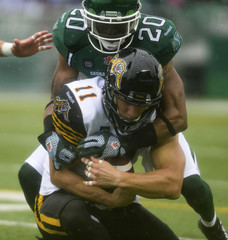 Tiger-Cats wide receiver Giguere is brought down by Roughriders corner back Maze during the first half of their CFL football game in Regina