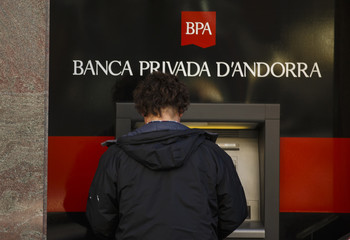 A man uses an ATM outside the headquarters of Banca Privada D'Andorra (BPA) in Escaldes-Engordany