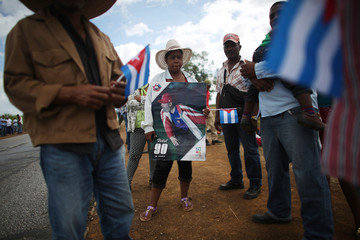 Farmer holds a picture of Fidel Castro as she and others await the arrival of the caravan carrying the late Cuban leader's ashes in Florida, Cuba