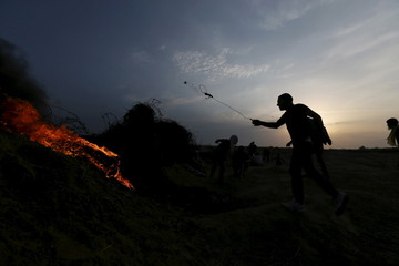 Palestinian protester uses a sling to hurl stones towards Israeli troops during clashes near the border between Israel and Central Gaza Strip