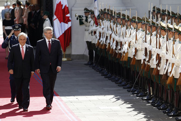 Chile's President Sebastian Pinera and Canada's Prime Minister Stephen Harper walk past an honor guard at the government palace in Santiago