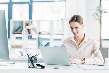 young smiling caucasian businesswoman working on laptop at office
