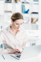young caucasian businesswoman working on laptop while sitting at office