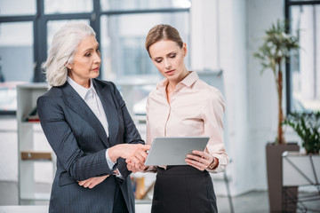 Senior businesswoman pointing at digital tablet and looking at young colleague