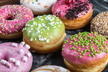 Glazed donuts with different fillings on a black table