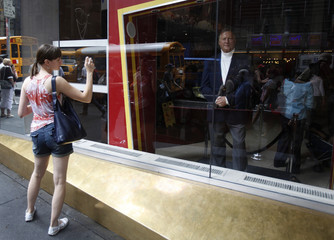 A tourist stops to take photographs of a wax figure of former New York Yankees owner George Steinbrenner at Madame Tussauds in New York
