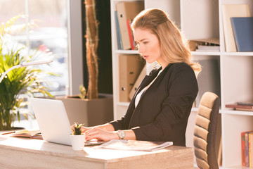 Focused young businesswoman using laptop at workplace