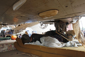 A man displaced by inter-communal violence rests under a plane in a camp for displaced persons at Bangui M'Poko International Airport