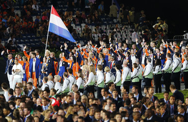 Netherlands' flag bearer Dorian van Rijsselberge holds the national flag as he leads the contingent in the athletes parade during the opening ceremony of the London 2012 Olympic Games at the Olympic Stadium