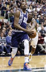 Oklahoma City Thunder forward Durant drives past Utah Jazz forward Carroll during the first half of their NBA basketball game in Salt Lake City, Utah