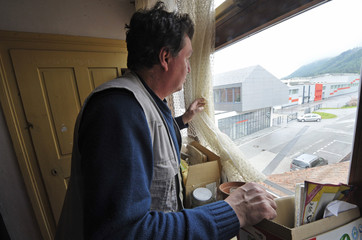 A former worker of the Metal Industry Vransko factory who is now unemployed, looks out from his apartment window towards his previous workplace in Vransko