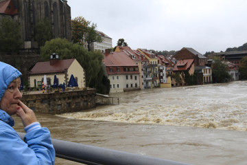 A woman watches the flooded Lusatian Neisse river in the town of Goerlitz