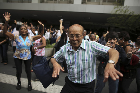 Elderly people dance on a street during the International Day of Older Persons in Sao Paulo