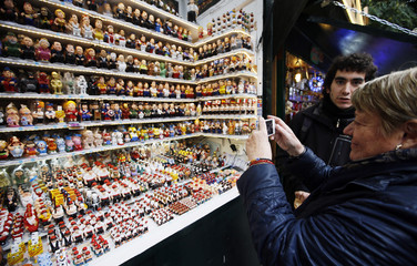 "A woman takes a picture of clay ""caganers"" figures at the Santa Llucia Christmas market in central Barcelona"