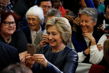 U.S. Democratic presidential candidate Hillary Clinton takes a selfie with the crowd while visiting La Escuelita School in Oakland, California