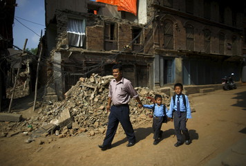Birendra Karmacharya walks his sons past the debris of collapsed houses as they head towards the school in Bhaktapur