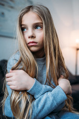 Pensive little girl in pajamas sitting with crossed arms and looking away
