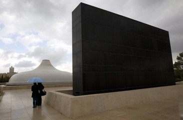 People stand under an umbrella in front of the Shrine of the Book at the Israel Museum in Jerusalem