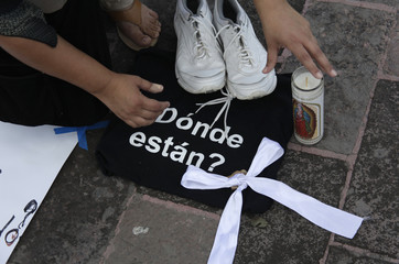 A woman arranges a pair of tennis shoes over a black bag during a protest for the killing of 49 people by hitmen in Cadereyta at the Macroplaza in Monterrey