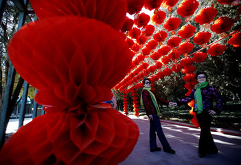Visitors pose for a picture next to paper lanterns celebrating the Chinese New Year celebrations at Ditan Park, also known as the Temple of Earth, in Beijing