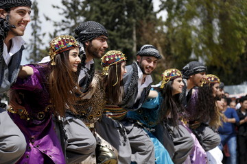 Kurdish dancers dance during a gathering celebrating Newroz, which marks the arrival of spring and the new year, in Al Jalaa Sports City in Damascus