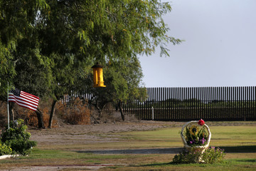 A U.S. flag blows in the wind in the backyard of a home facing the border fence at the United States-Mexico border outside of Brownsville