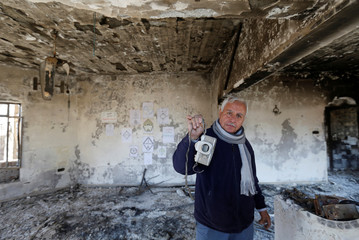 An Iraqi Christian man shows his old camera at his house, which was burned by Islamic State militants before they fled the area, in Qaraqosh, Iraq