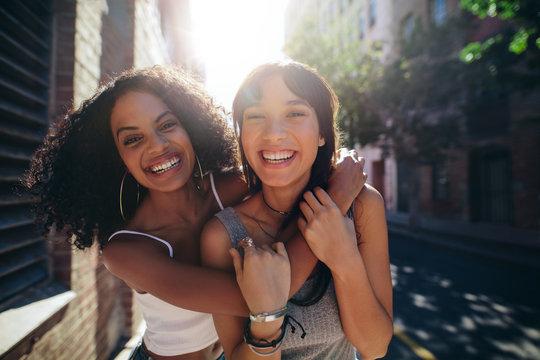 Two young women having fun on city street