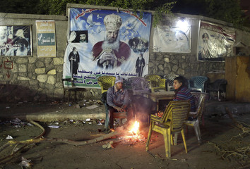 Coptic Orthodox Christians sit near fire to warm up in front of a banner with a picture of Pope Shenouda III near Pope Samaan monastery in Cairo