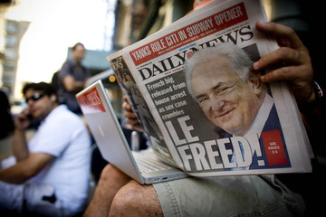 A man reads the New York Daily News, which features former IMF chief Strauss-Kahn on the front page, in Manhattan