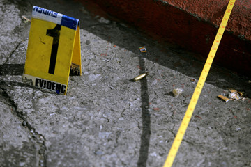 Evidence marker sits next to a bullet casing at a crime scene where five prison guards were gunned down by unknown assailants in Guatemala City