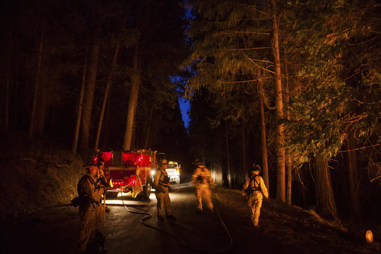 A firefighting crew watches a back fire after sunset on the rim fire near Buck Meadows
