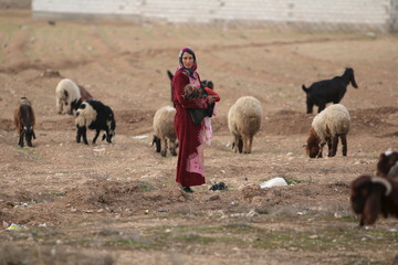 A woman carries a child while guiding sheep in Ain-Hosn village