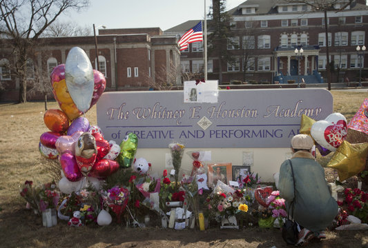 Well-wisher leaves flower at monument to late singer Houston in front of Whitney E. Houston Academy of Creative and Performing Arts in East Orange