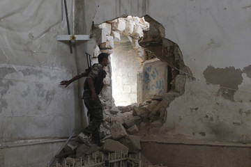 A Free Syrian Army fighter goes through a hole in the wall heading towards the frontline in Old Aleppo