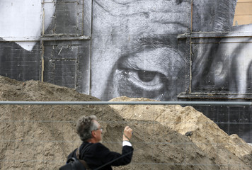 Man photographs creation by French artist J.R. near the Berlin cathedral in Berlin