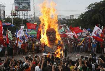 An effigy of President Aquino burns during a protest near the House of Representatives in Quezon City