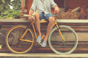 Young attractive man enjoying outdoors with old bicycle.