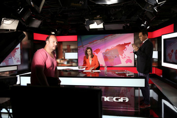 News anchor Sarafoglou, journalist Takis and a cameraman are seen during an interval of a news broadcast at a studio of Greek private channel MEGA in Athens