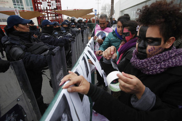 Demonstrators place pictures of missing women on a barrier as federal policemen stand guard during a protest against the visit of Mexico's President Enrique Pena Nieto to the city, in Ciudad Juarez