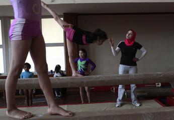 A coach trains girls in a gymnastics hall in Alexandria