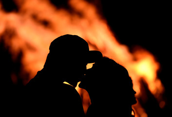 A couple kissing in front of bonfire during the traditional San Juan's night in Gijon